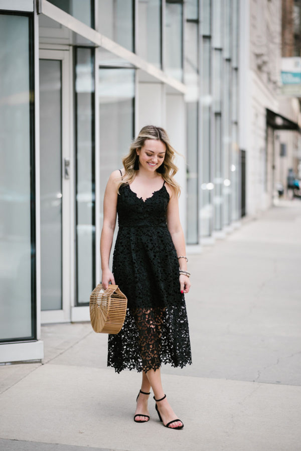 Bows & Sequins wearing a black lace dress for summer wedding guest attire.