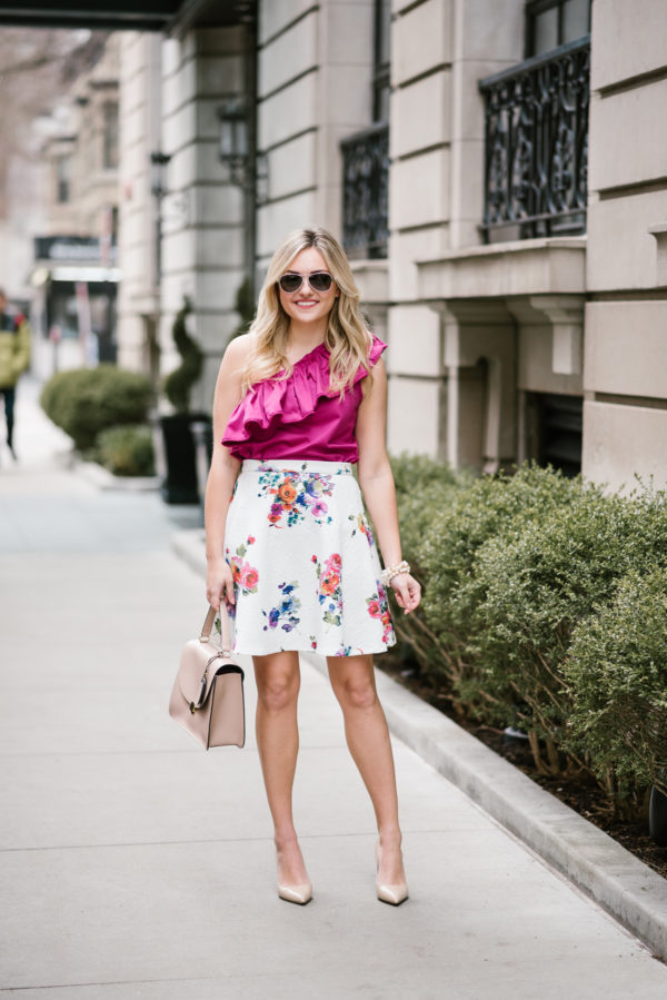 Bows & Sequins styling a fuchsia one-shoulder ruffled top with a floral skirt and nude pumps in Chicago.