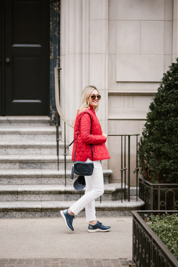 Bows & Sequins wearing a Barbour quilted red jacket, white jeans, a Gucci crossbody bag, and navy blue sneakers.