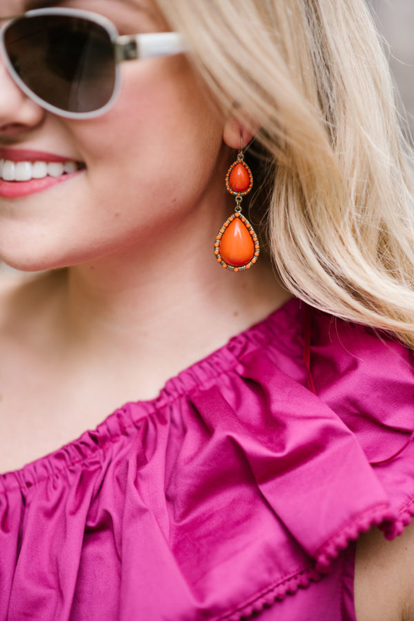 Lifestyle blogger Bows & Sequins wearing coral statement earrings with a fuchsia top.