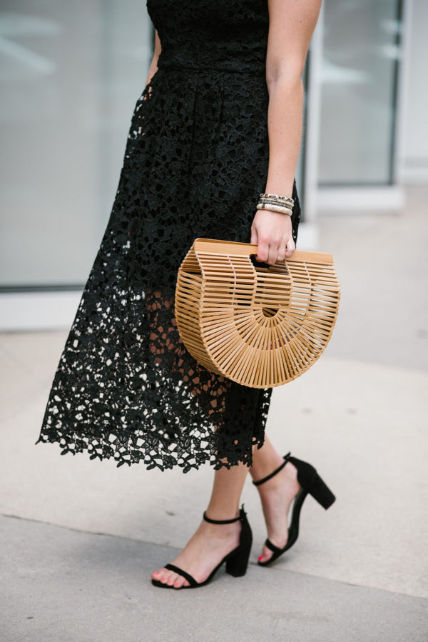 Bows & Sequins wearing a black lace dress with a Cult Gaia bag.