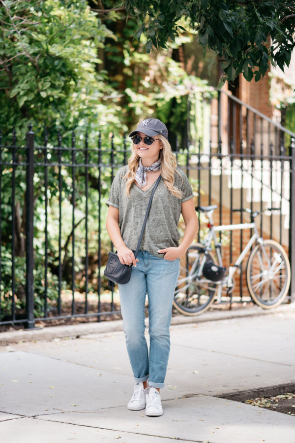 Travel writer Bows & Sequins wearing boyfriend jeans and a casual tee with a bandana and baseball hat while sightseeing in Amsterdam.