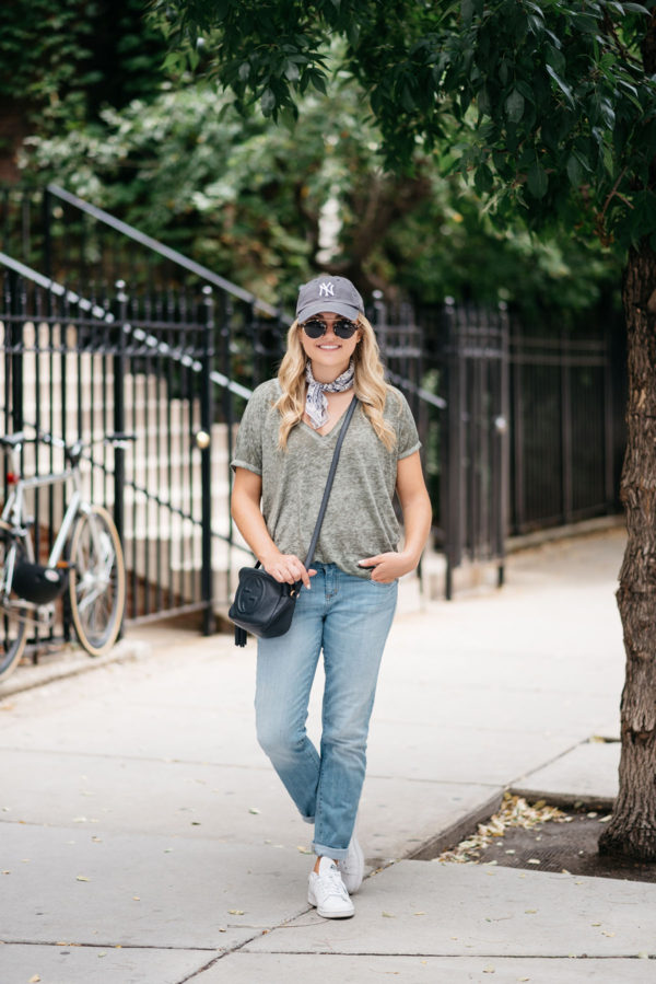 Jessica of Bows & Sequins wearing a Yankees baseball hat, boyfriend jeans, and Stan Smith sneakers.
