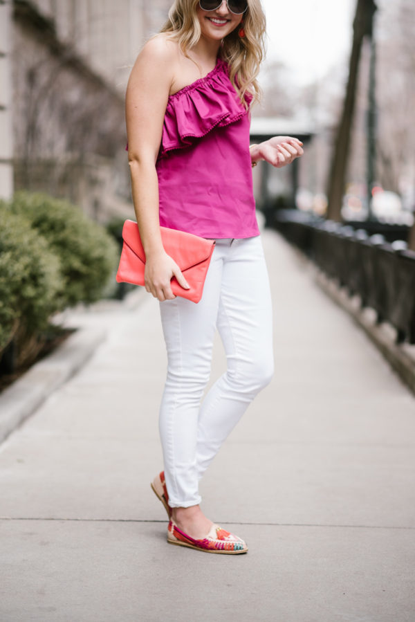 Bows & Sequins wearing a Devlin ruffled top with white jeans and a coral envelope clutch.