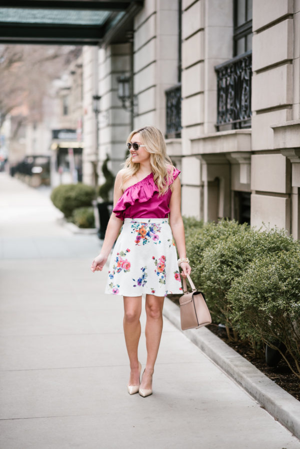 Jessica wearing a fuchsia Devlin top and a Bows & Sequins floral skirt with Kate Spade pumps.