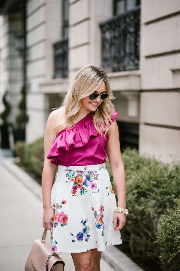Jessica styling a fuchsia ruffled top with a white floral skirt and a blush pink satchel.