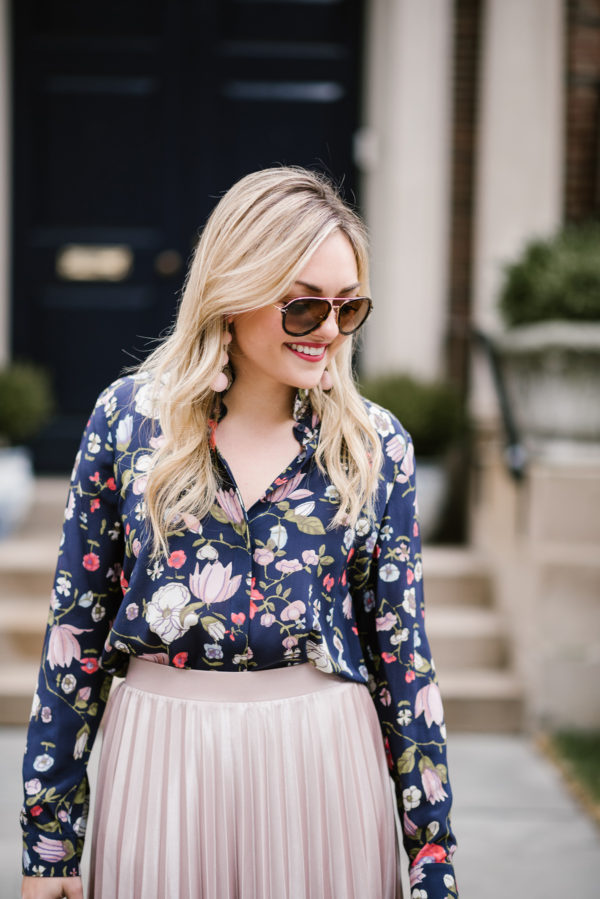Bows & Sequins wearing a pink pleated midi skirt, a floral blouse, and tortoise Celine aviators.