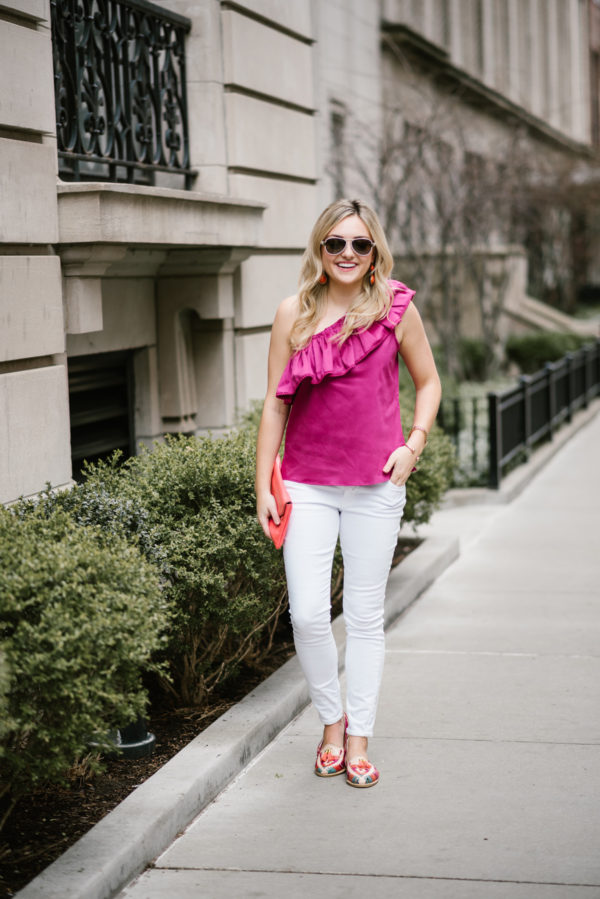 Bows & Sequins styling a ruffled Devlin one-shoulder top with white denim from Old Navy and a J.Crew coral clutch.