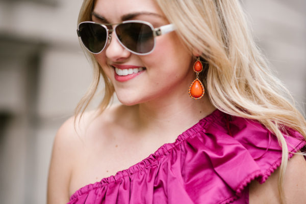 Bows & Sequins wearing coral statement earrings and a fuchsia ruffled top.