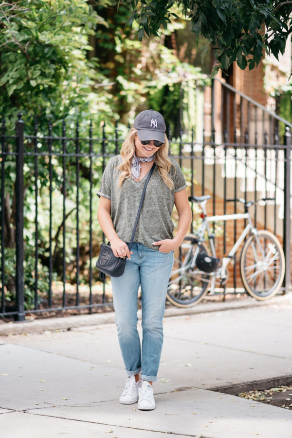 Fashion blogger Bows & Sequins wearing a casual outfit for sightseeing in Europe: Yankees baseball cap, casual v-neck tee, printed bandana, and boyfriend jeans.