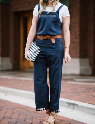 Bows & Sequins styling a navy blue jumpsuit with a white tee underneath.