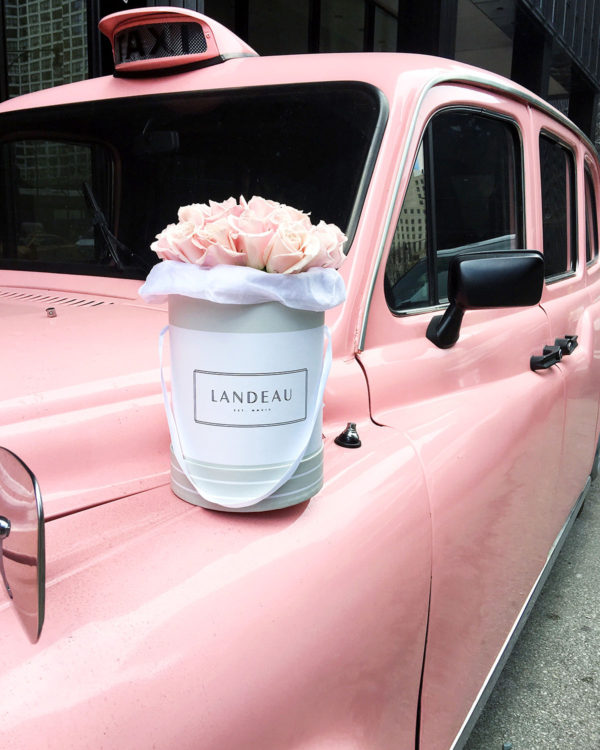 Bows & Sequins Instagram photo of Landeau blush pink roses in a shoe box in front of the pink taxi at the Langham luxury hotel in Chicago