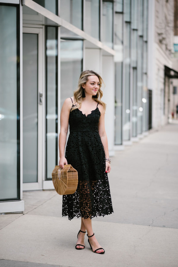 Bows & Sequins wearing a black lace dress with fringe tassel earrings.