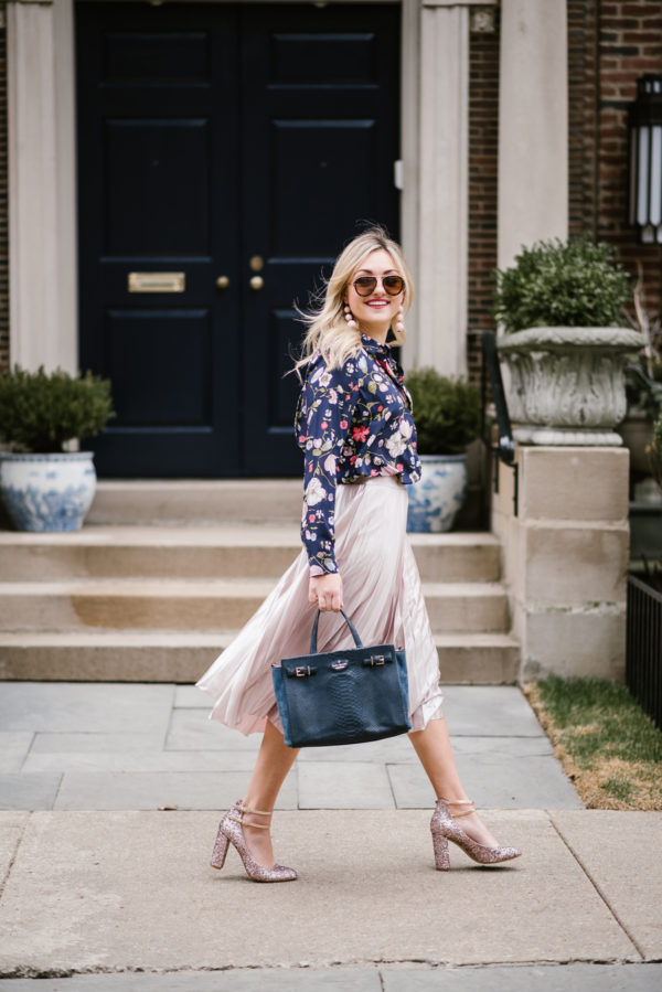Fashion blogger Bows & Sequins wearing a navy floral blouse and a blush pink midi skirt with glitter pink Kate Spade pumps.