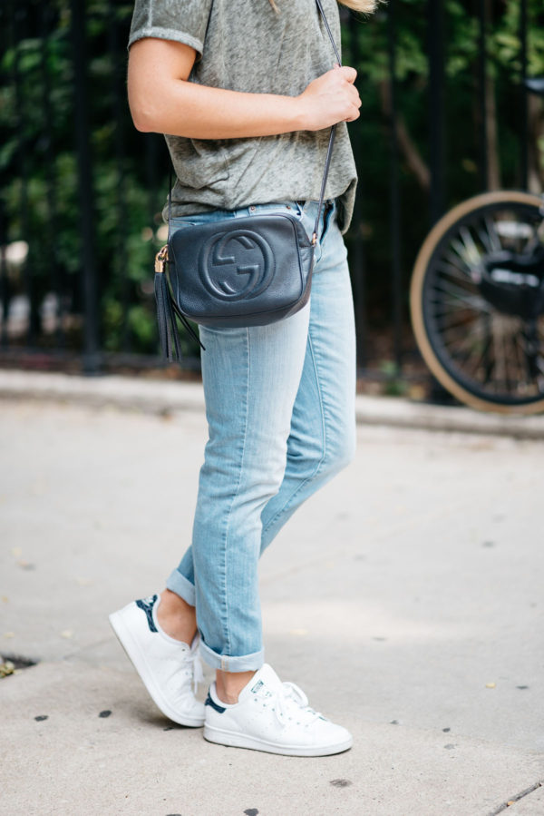 Jessica from Bows & Sequins wearing cuffed boyfriend jeans, a navy Gucci Soho disco bag, and white Stan Smith sneakers.