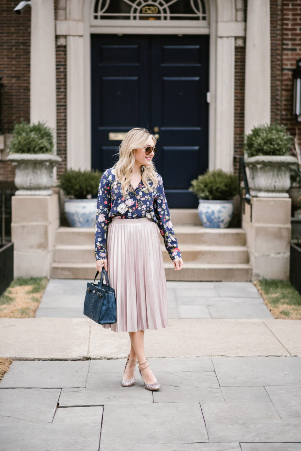 Bows & Sequins wearing a blush pink midi skirt, navy floral top, and glitter heels.