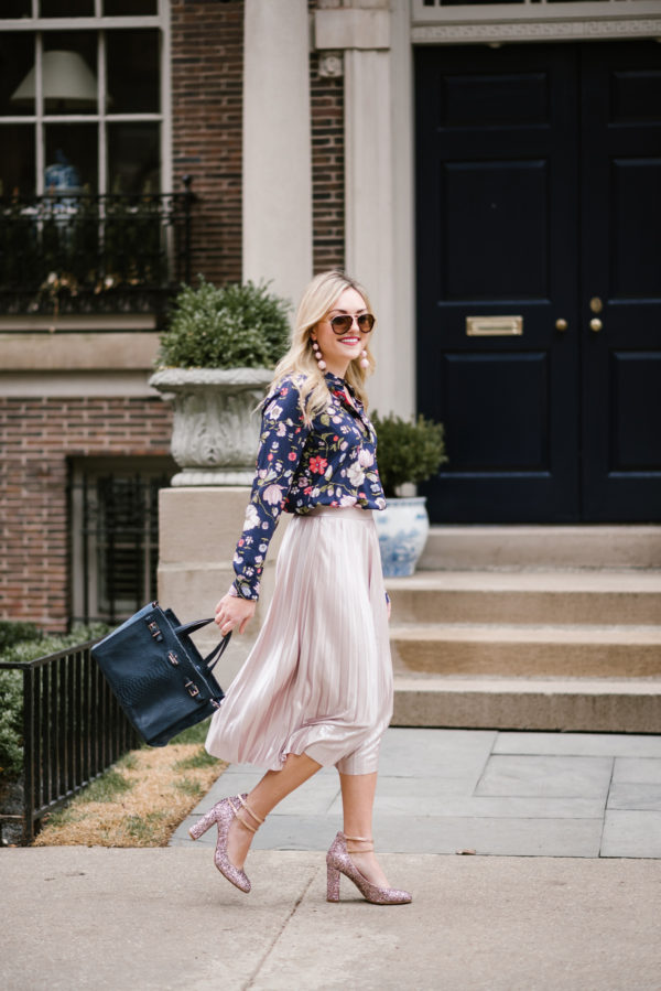 Bows & Sequins wearing a pink pleated midi skirt and floral blouse with a navy handbag and Kate Spade pumps.