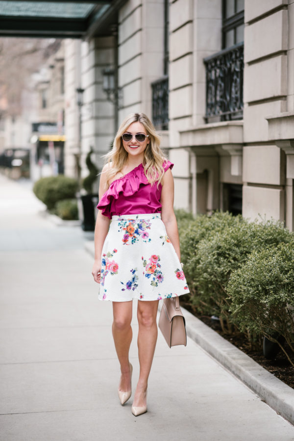 Jessica wearing a floral Bows & Sequins collection skirt and a blush pink handbag.
