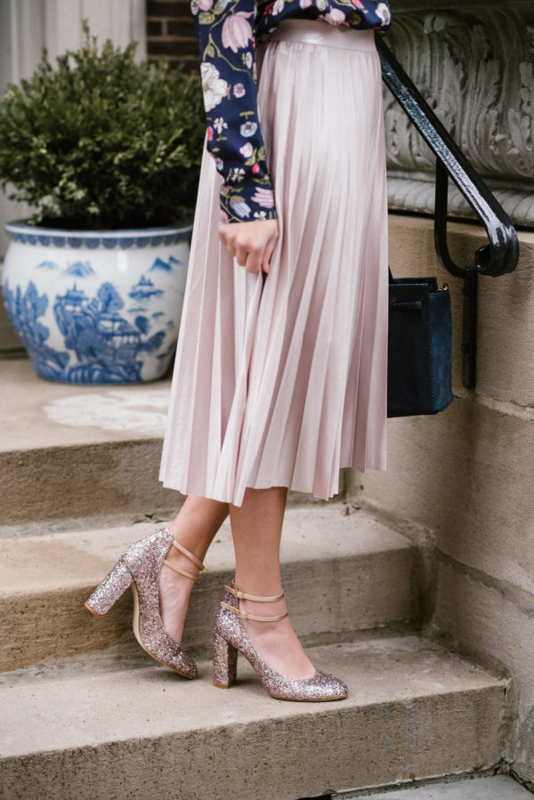 Chicago style blogger Bows & Sequins wearing a pink pleated midi skirt and blush pink glitter pumps.