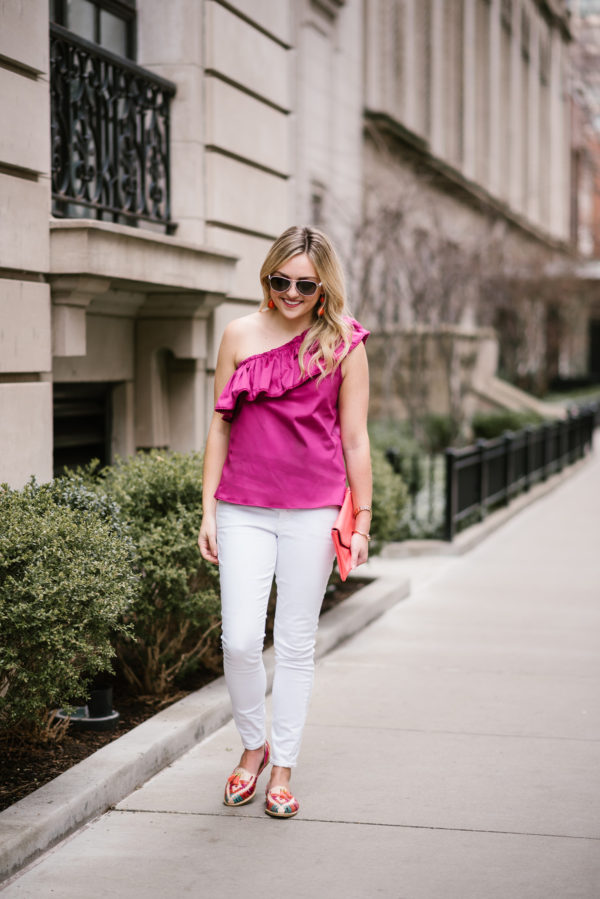 Bows & Sequins wearing a fuchsia one-shoulder top with white jeans and leather loafers from Mexico.