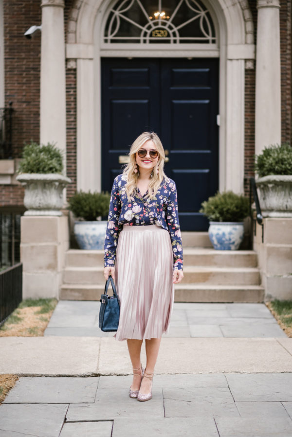Bows & Sequins wearing a Rebecca Taylor floral blouse with a Rachel Roy pink pleated skirt and a navy blue KSNY handbag.
