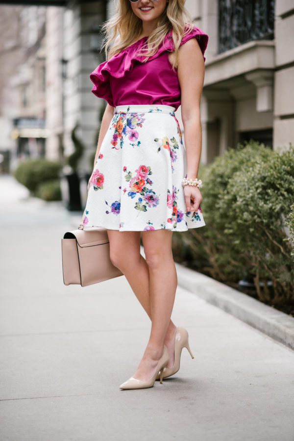 Jessica Sturdy wearing a Bows & Sequins floral skirt with nude heels and a blush pink Cuyana satchel.