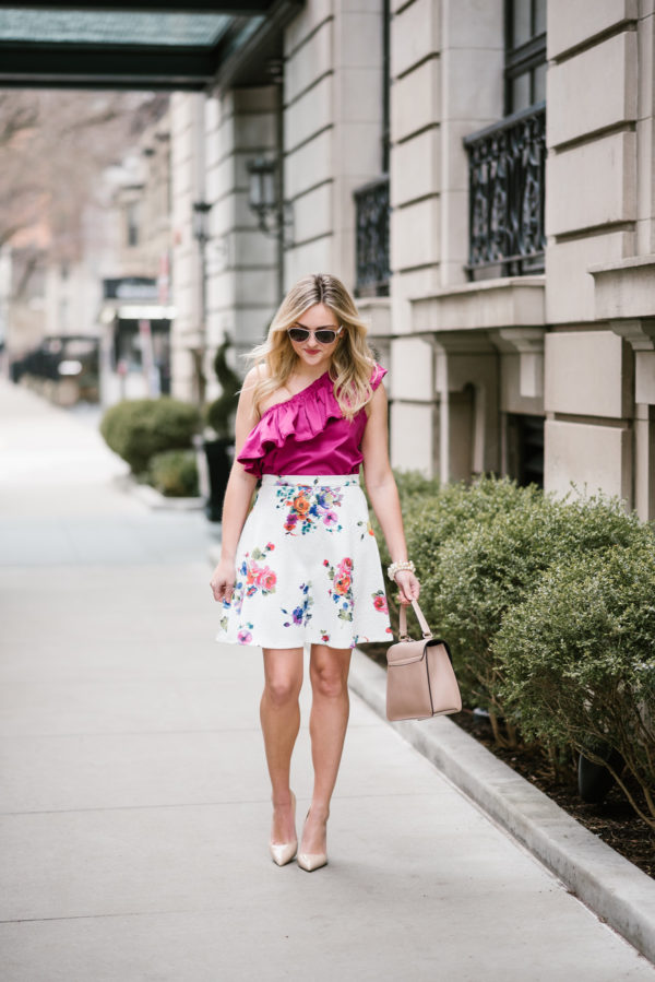Chicago blogger Bows & Sequins wearing a Devlin one-shoulder top with a floral printed skirt and a blush pink satchel.