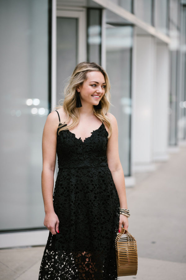 Bows & Sequins styling a black lace dress with long tassel earrings.