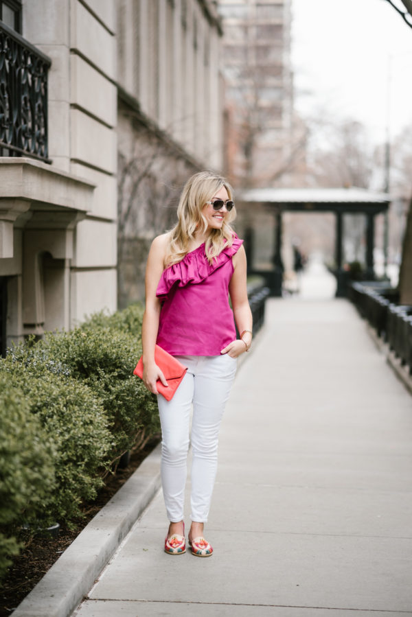 Bows & Sequins wearing a one-shoulder top and white jeans with Mexican loafers and a coral clutch.