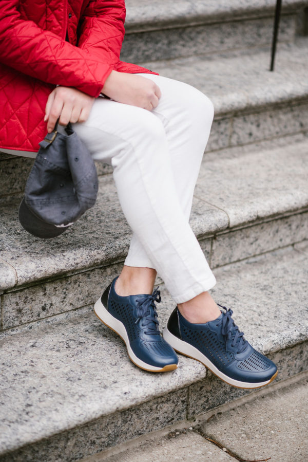 Bows & Sequins styling a pair of white corduroys with a red quilted jacket and navy blue leather sneakers.
