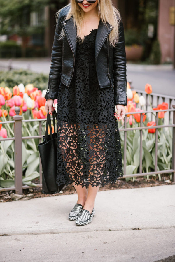 Lifestyle blogger Jessica of Bows & Sequins styling a black lace dress from Nordstrom with a Topshop moto jacket, a leather tote, and Kate Spade loafers.