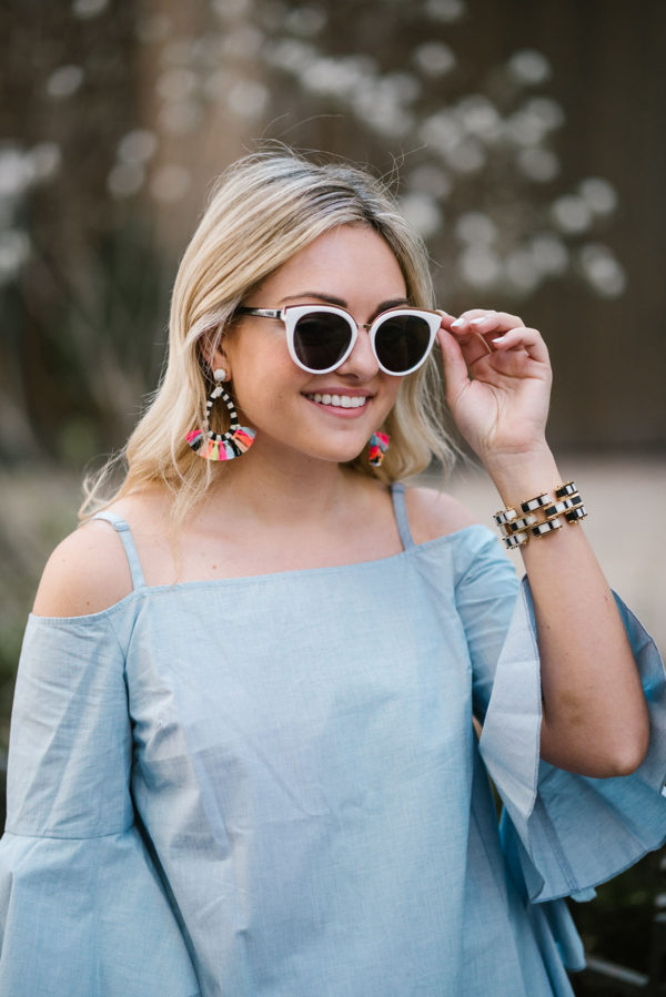 Lifestyle blogger Jessica Sturdy wearing colorful BaubleBar fringe earrings and a chambray Kensie top.