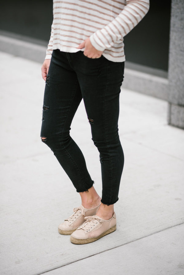 Travel writer Bows & Sequins wearing black raw hem jeans from Old Navy with a Kenzie striped sweater and Marc Fisher espadrille sneakers.