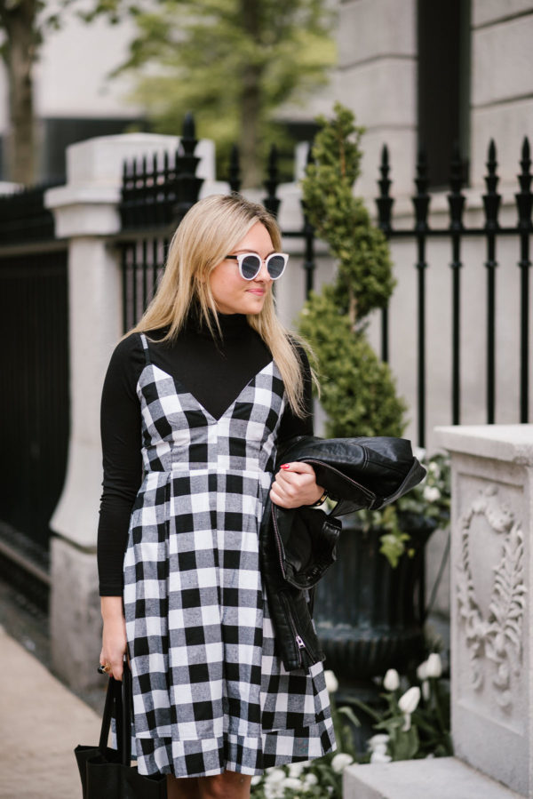 Fashion blogger Bows & Sequins wearing black and white sunglasses, a gingham dress, and black turtleneck top.