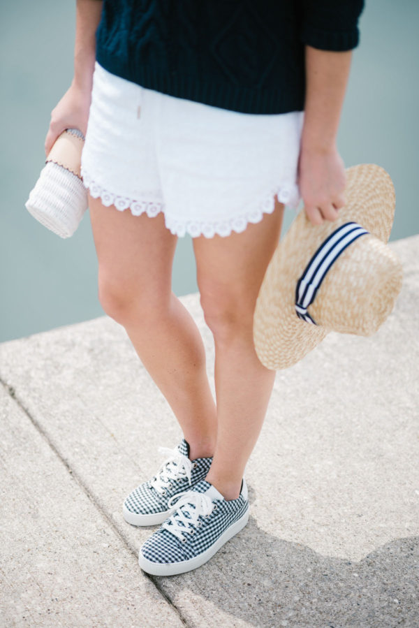 Fashion blogger Bows & Sequins wearing white Kensie eyelet shorts with a striped straw hat, a Vineyard Vines wicker clutch, and blue gingham sneakers.