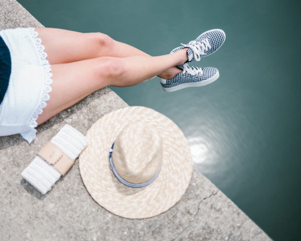 Lifestyle blogger Bows & Sequins wearing eyelet shorts and gingham sneakers with a white Vineyard Vines wicker clutch and a straw hat.