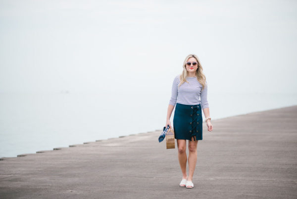 Jessica of Bows & Sequins, a style blog, wearing a Lands End striped tee with a Kensie lace-up skirt and white Kurt Geiger slides along Lake Michigan in Chicago.