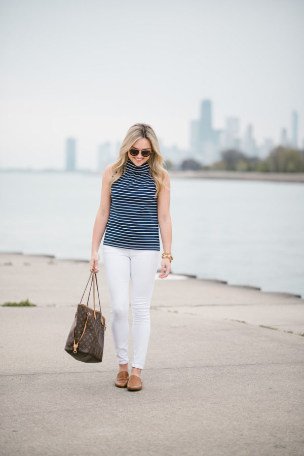 Jessica of Bows & Sequins, a fashion-focused lifestyle blog, wearing a Sail to Sable striped top with Old Navy white denim, a Louis Vuitton Neverfull bag, and Dune London leather loafers.