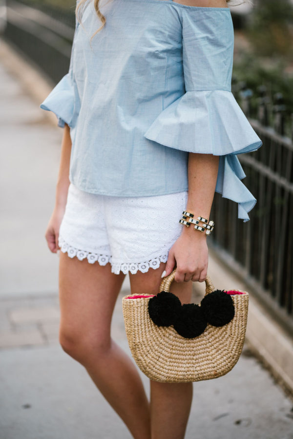 Bows & Sequins wearing an off-the-shoulder chambray top with Kensie eyelet shorts and a JadeTribe pom pom bag.