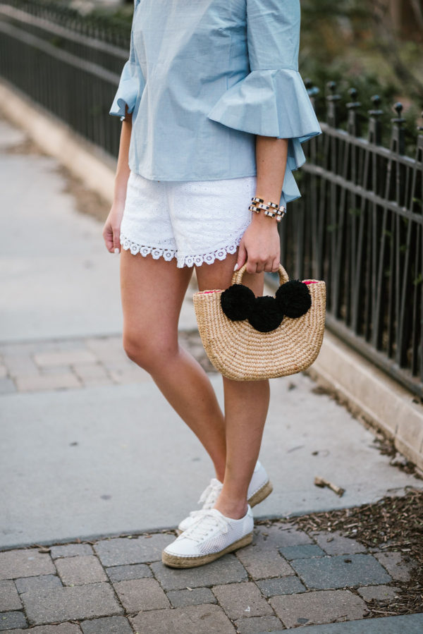 Bows & Sequins wearing a Kensie chambray top with white eyelet shorts, a JadeTribe pom pom basket bag, and Marc Fisher espadrilles.