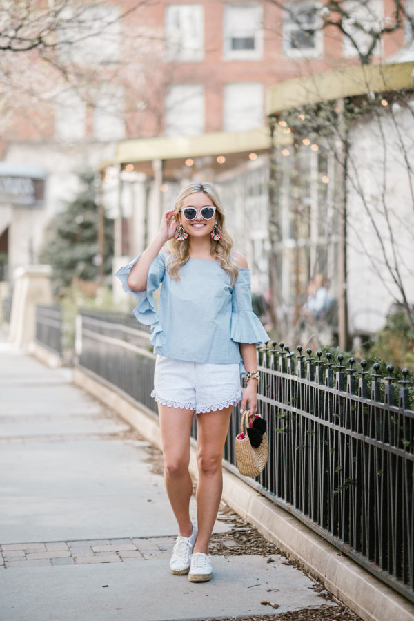 Bows & Sequins styling a casual summer outfit with a Kensie bell sleeve top, white eyelet shorts, white espadrille shoes, and a pom pom handbag.