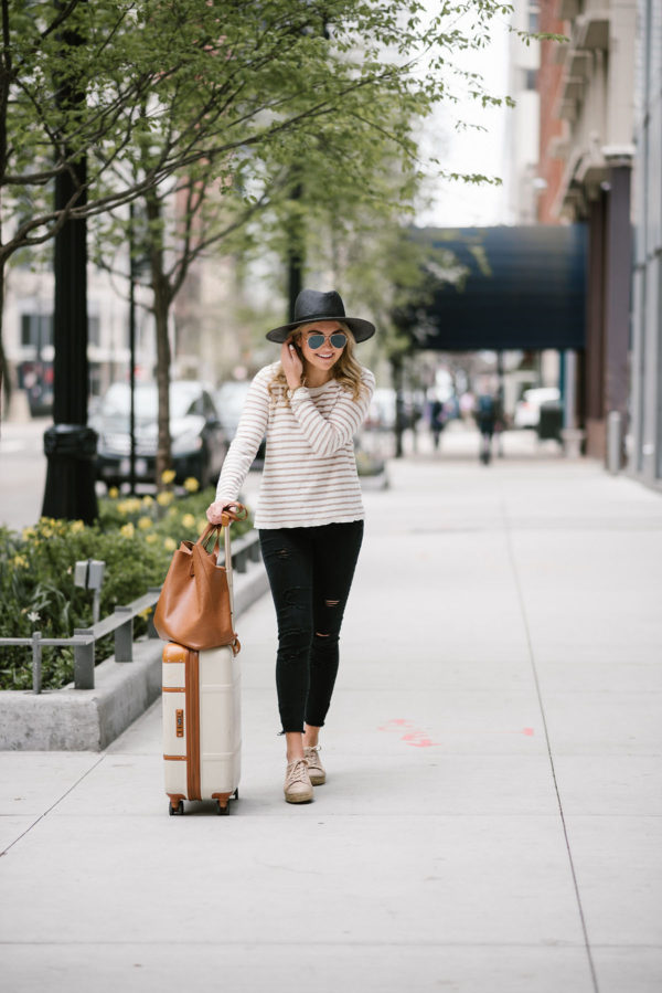 Bows & Sequins sharing her go-to travel outfit: straw hat, striped sweater, raw hem jeans, and espadrille sneakers.