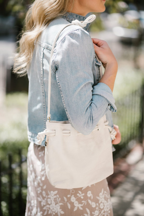 Fashion blogger Bows & Sequins styling a white Clare V Petit Henri bag for a music festival.