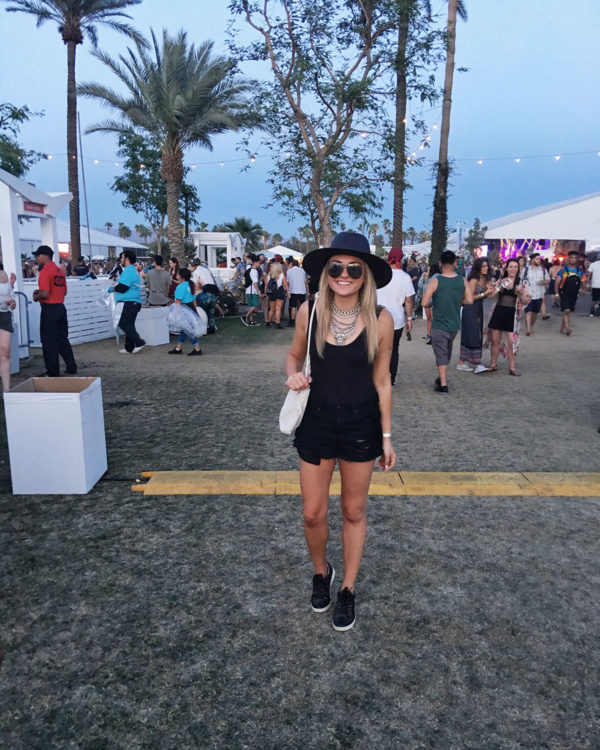 Bows & Sequins wearing a black hat, bodysuit, cut offs, and a statement necklace at Coachella music festival.
