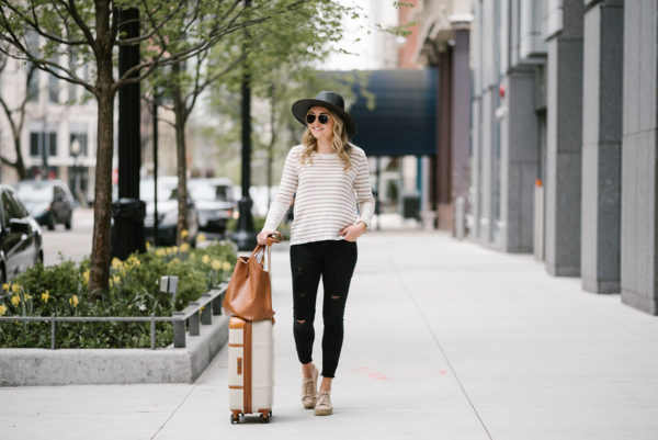 Travel blogger Bows & Sequins styling a Kenzie striped sweater, black jeans, espadrille platform sneakers, and a straw hat for traveling with a Cuyana tote and Brics suitcase.