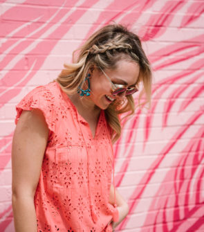 Bows & Sequins wearing a coral eyelet top, sunglasses from Hadid Eyewear, and BaubleBar statement earrings in front of the pink flamingo wall in Chicago