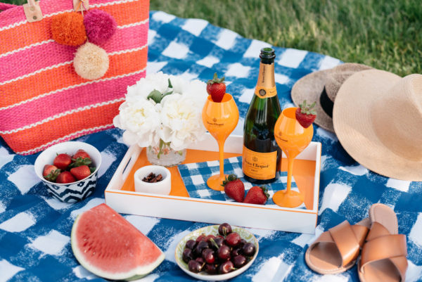 Blue gingham Crate & Barrel picnic blanket with an orange lacquer tray and orange champagne flutes with a Mar y Sol striped tote.