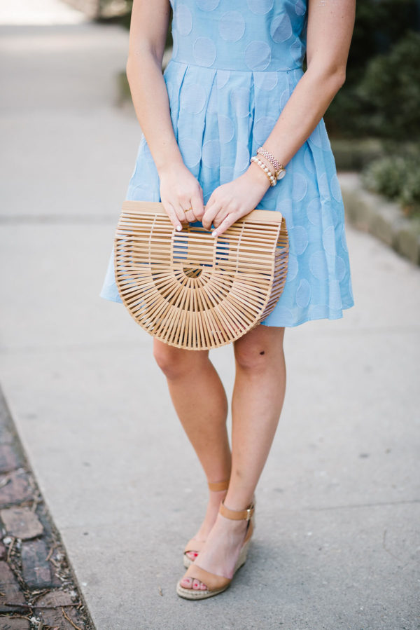 Lifestyle blogger Bows & Sequins styling a hydrangea blue dress with a Cult Gaia Bamboo Arc bag and Vince Camuto leather ankle strap wedge sandals.