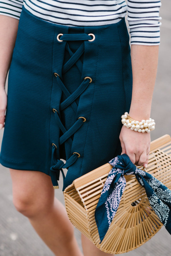 Fashion writer Bows & Sequins styling a navy Kensie lace-up skirt with a Cult Gaia bamboo bag, a navy bandana, and a Sweet & Spark pearl bracelet.