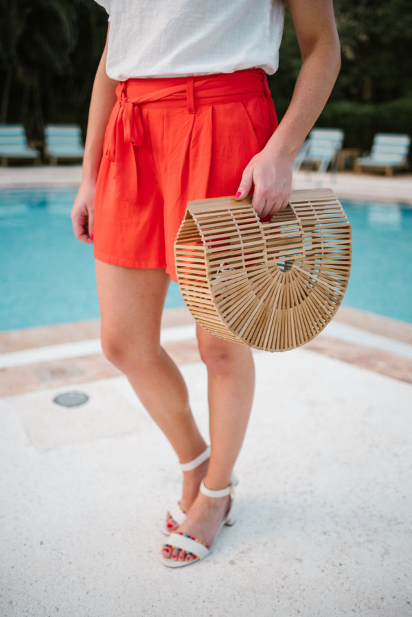 Travel blogger Bows & Sequins holding a Cult Gaia bamboo Ark bag and wearing orange tie-waist shorts and J.Crew pom pom sandals.